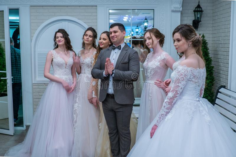A toastmaster posing for the camera among the bride models. At the Wedding hassle 2019 exhibition took place in Kirov, Russia royalty free stock photo