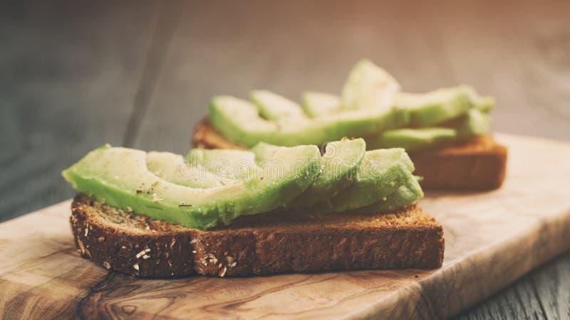 Toastroggenbrot mit geschnittener Avocado und Kräutern lizenzfreies stockfoto