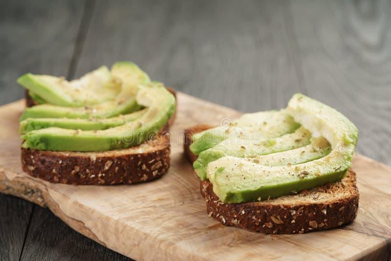 Toastroggenbrot mit geschnittener Avocado und Kräutern stockbild