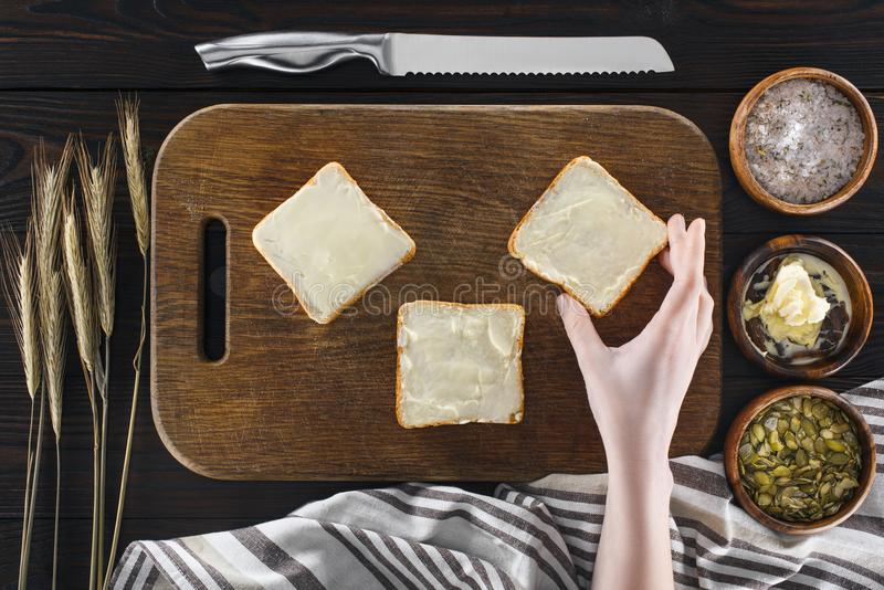 Toasts with butter and human hand stock images