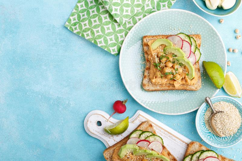 Toasts with chickpea hummus, avocado, fresh radish, cucumber, sesame seeds and flaxseed sprouts. Diet breakfast. Delicious and hea stock images