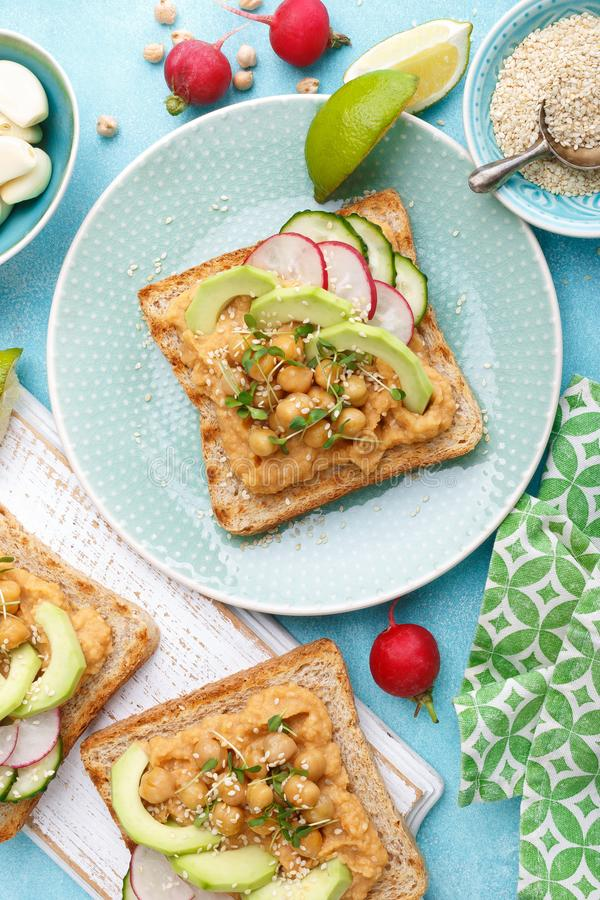 Toasts with chickpea hummus, avocado, fresh radish, cucumber, sesame seeds and flaxseed sprouts. Diet breakfast. Delicious and hea stock image
