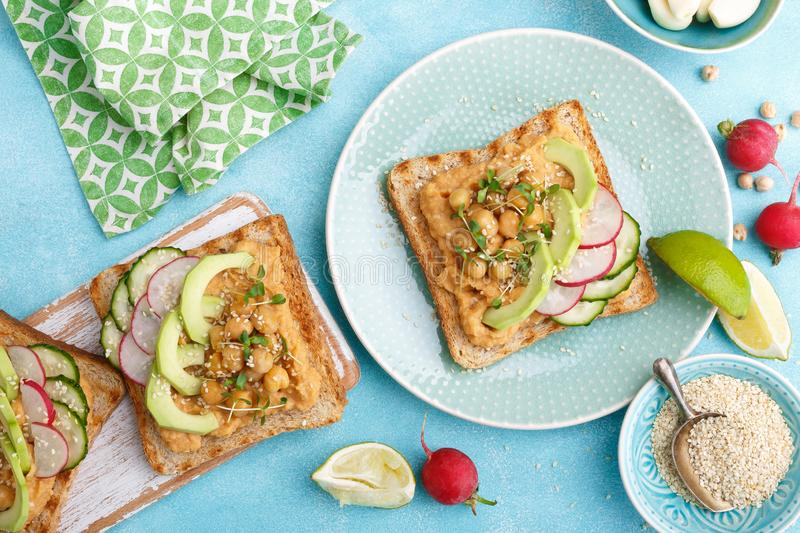 Toasts with chickpea hummus, avocado, fresh radish, cucumber, sesame seeds and flaxseed sprouts. Diet breakfast. Delicious and hea royalty free stock image