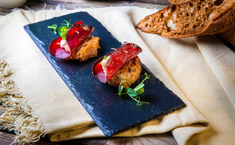 Toasts with a circle of beets, goat cheese and a piece of salmon. On a black slate on a background of rustic napkin.Decorated with shoots of green peas leaves stock image