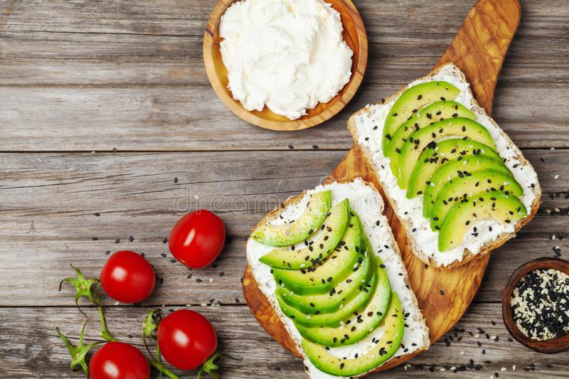Toasts with creamy cheese and avocado for healthy snack or breakfast. Top view royalty free stock image