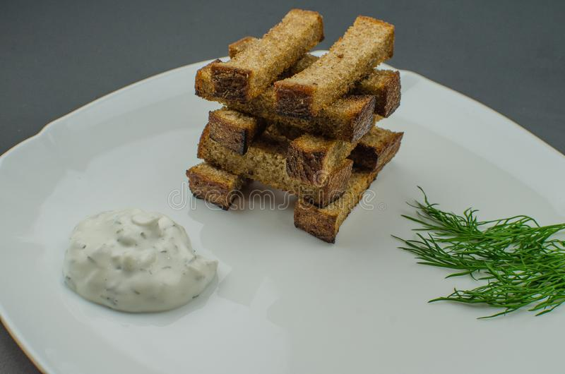 Toasts are fried on a frying pan with spices. Served on a white plate with garlic sauce and barbecue sauce. Toasts are fried on a frying pan with spices. Served stock image