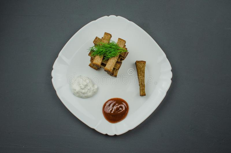Toasts are fried on a frying pan with spices. Served on a white plate with garlic sauce and barbecue sauce. Toasts are fried on a frying pan with spices. Served royalty free stock images