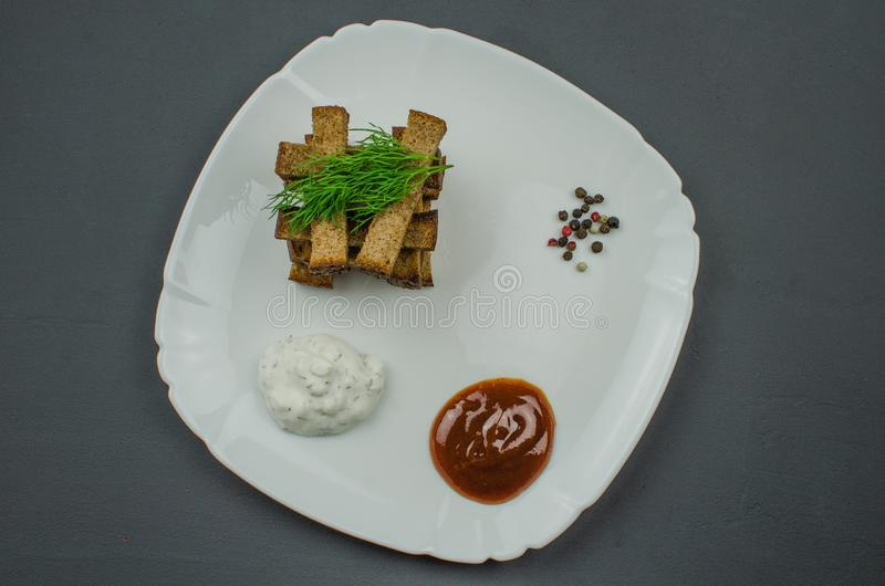 Toasts are fried on a frying pan with spices. Served on a white plate with garlic sauce and barbecue sauce. Toasts are fried on a frying pan with spices. Served stock images