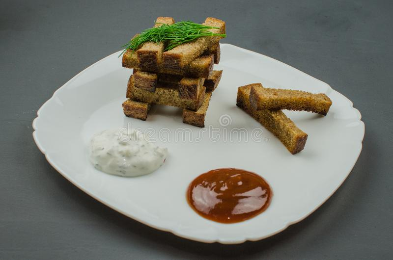 Toasts are fried on a frying pan with spices. Served on a white plate with garlic sauce and barbecue sauce. Toasts are fried on a frying pan with spices. Served stock photography