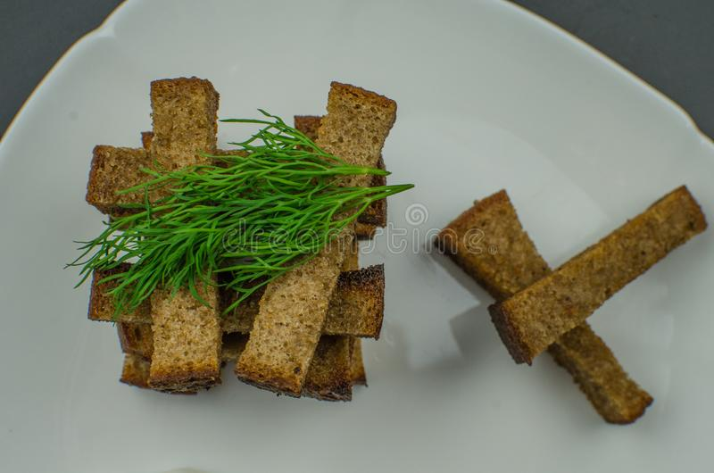 Toasts are fried on a frying pan with spices. Served on a white plate with garlic sauce and barbecue sauce. Toasts are fried on a frying pan with spices. Served royalty free stock photography