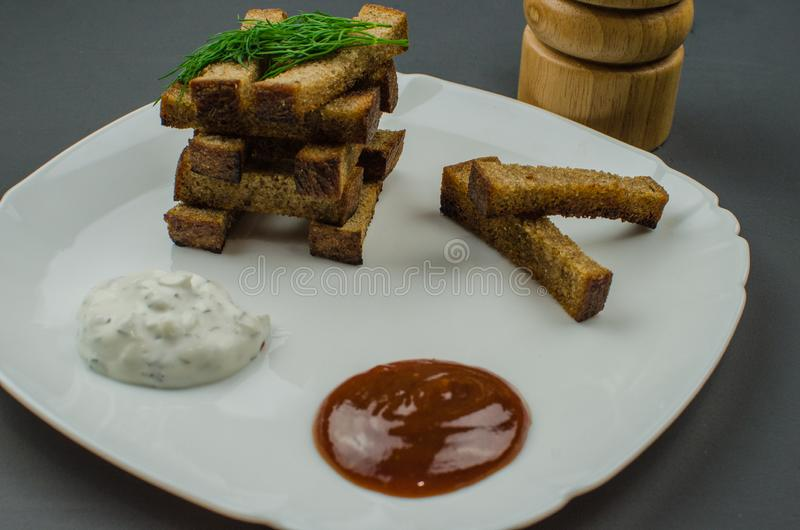 Toasts are fried on a frying pan with spices. Served on a white plate with garlic sauce and barbecue sauce. Toasts are fried on a frying pan with spices. Served stock photos