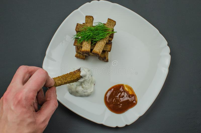 Toasts are fried on a frying pan with spices. Served on a white plate with garlic sauce and barbecue sauce. Toasts are fried on a frying pan with spices. Served stock photo