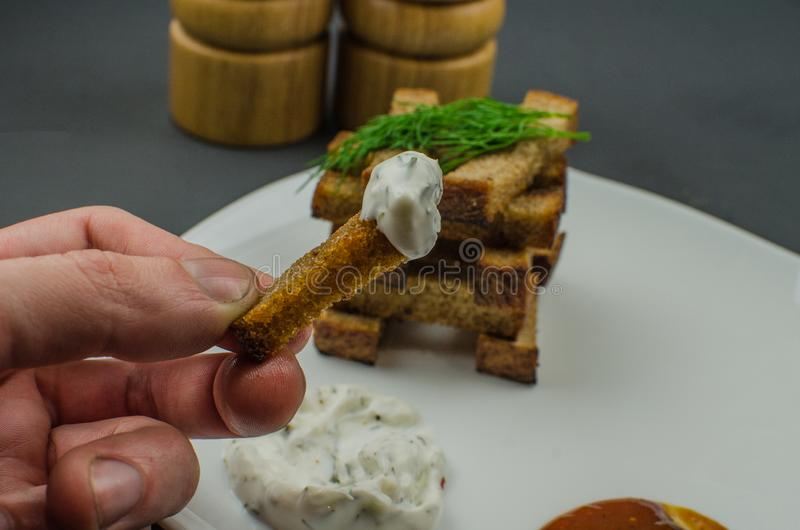 Toasts are fried on a frying pan with spices. Served on a white plate with garlic sauce and barbecue sauce. Toasts are fried on a frying pan with spices. Served royalty free stock photo