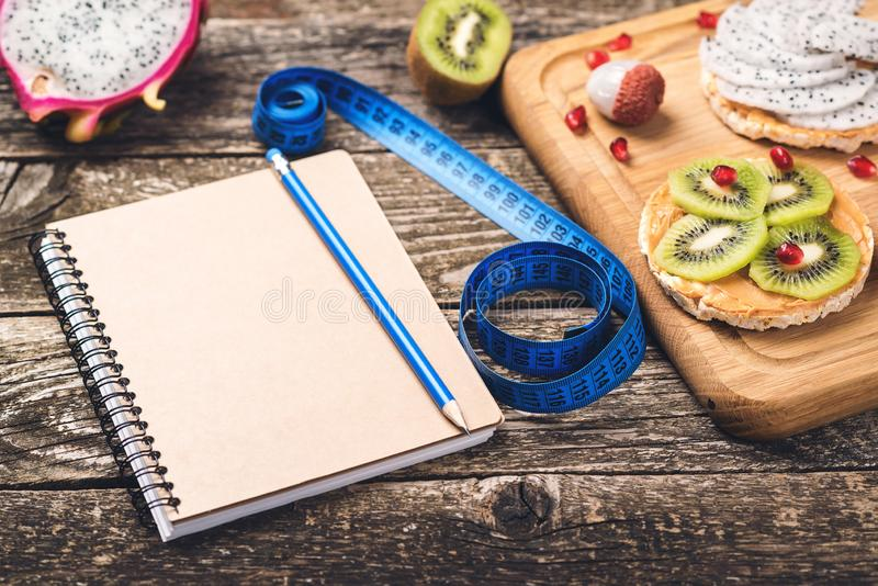 Toasts with fruit, measuring tape and empty notebook on wooden background. Slimming plan with fruits. Planning healthy diet royalty free stock photo