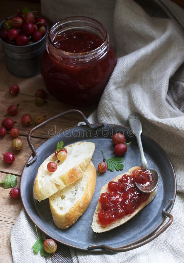 Toasts with gooseberry jam and gooseberries on a tin tray. Rustic style. Selective focus stock images