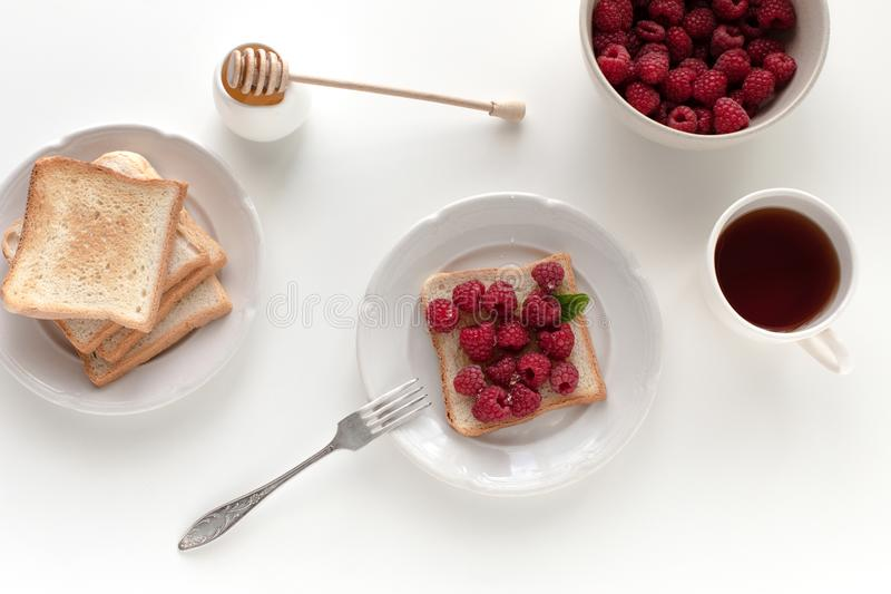 Toasts with raspberries for breakfast. Top view of toasts with raspberries for breakfast with tea, isolated on white royalty free stock photography