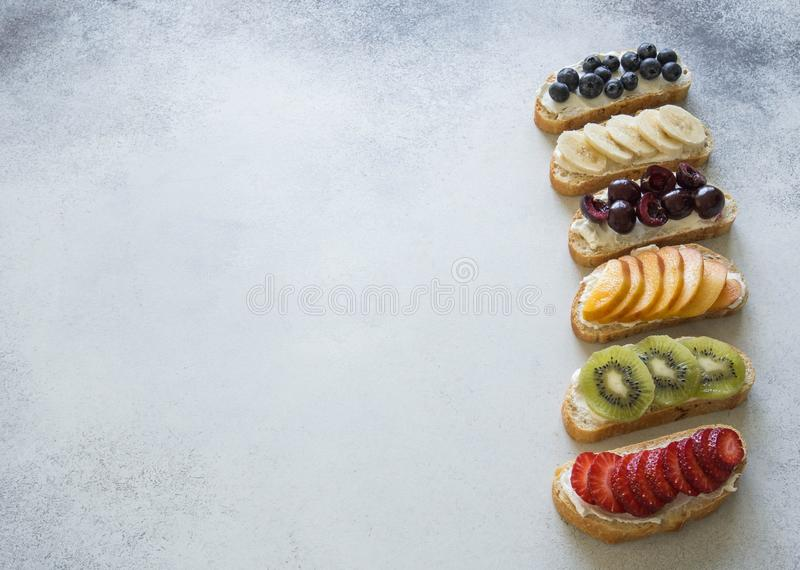 Toasts with various berries and fruits and cream cheese royalty free stock images