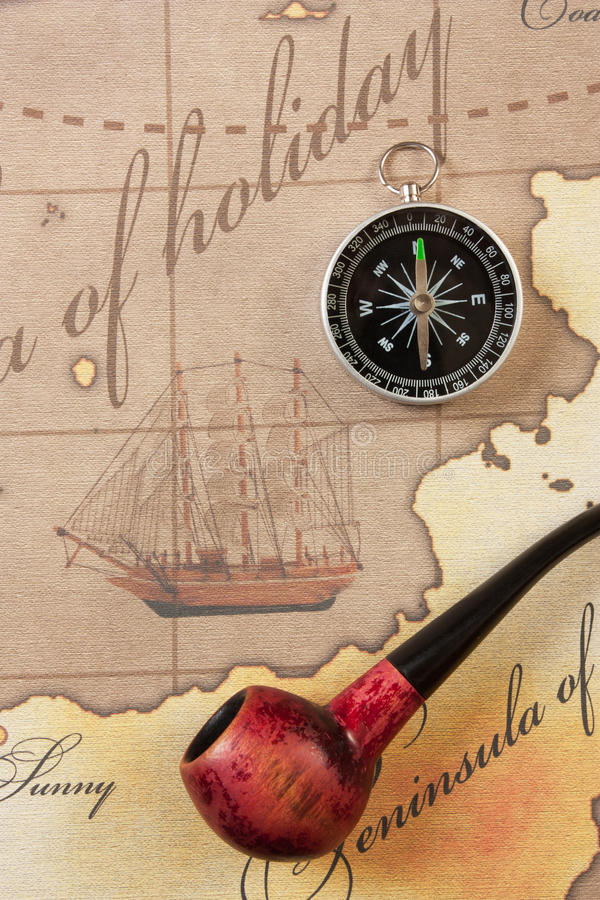 Tobacco pipe and compass on map. Tobacco pipe and a compass on the map stock photo