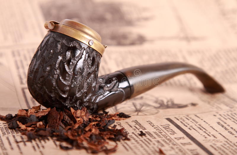 Tobacco pipe on old paper. Shallow depth of field stock photography