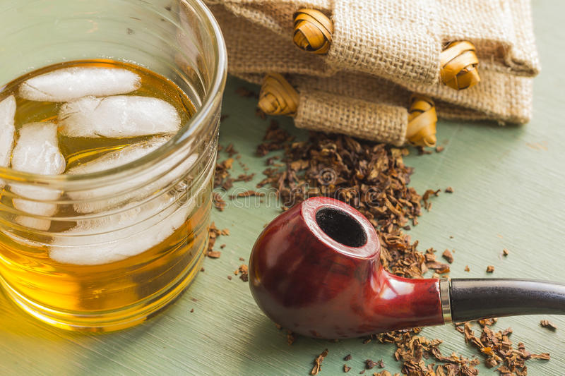 Tobacco Pipe and Whisky. Tobacco pipe on rustic warn green wood surface with spilled natural tobacco and a glass of whisky on the rocks royalty free stock images
