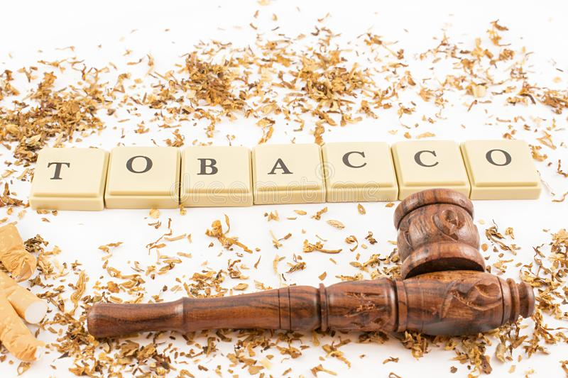 Tobacco, pipe and cigarette . Tobacco written with tokens, cigarette butts and wooden pipe on white background stock images