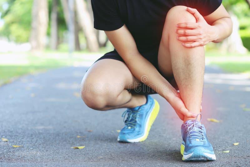 Tobillo torcido del corredor o roto doloroso conmovedor Accidente de entrenamiento del corredor del atleta El tobillo de funciona imagen de archivo