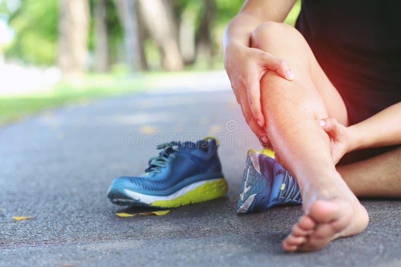 Tobillo torcido del corredor o roto doloroso conmovedor Accidente de entrenamiento del corredor del atleta El tobillo de funciona fotos de archivo libres de regalías