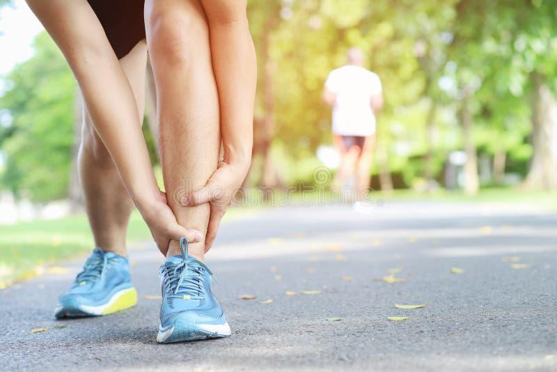 Tobillo torcido del corredor o roto doloroso conmovedor Accidente de entrenamiento del corredor del atleta El tobillo de funciona imágenes de archivo libres de regalías