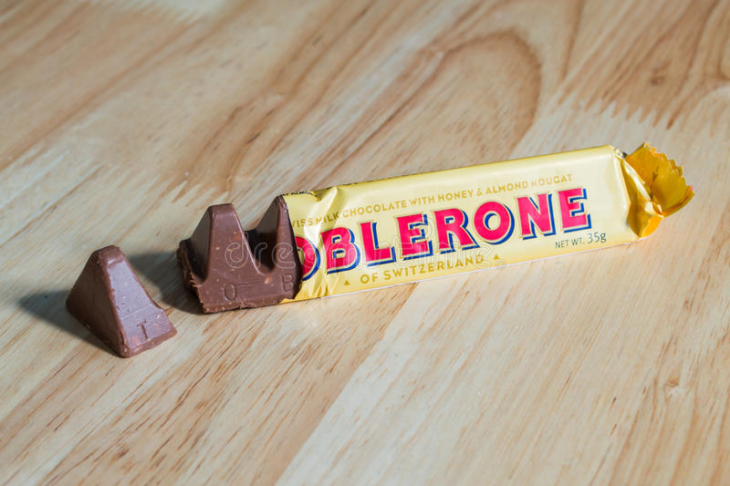 TOBLERONE. Bangkok, Thailand - November 28, 2016: A bar of Toblerone - Swiss milk chocolate with honey and almond nougat on a wood background stock image