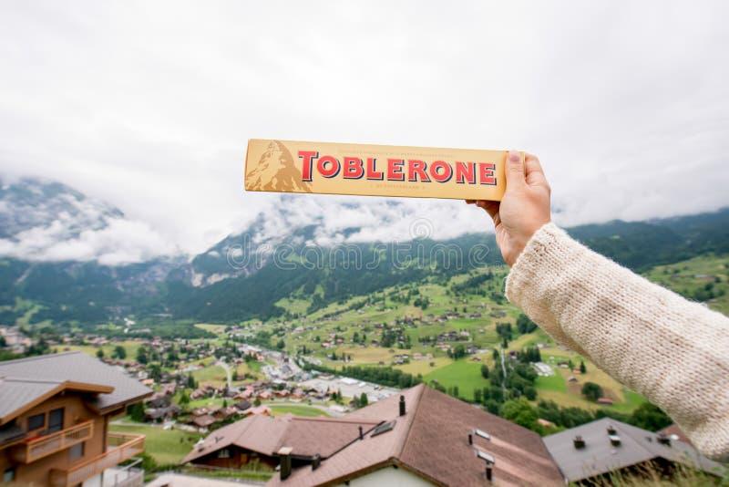 Toblerone bar chocolate. Grindelwald, Switzerland - June 26, 2016 Female hand holds Toblerone chocolate on the mountains background in Switzerland. Toblerone is stock photos