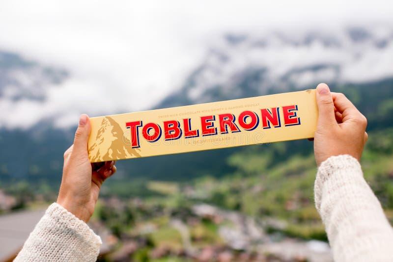 Toblerone bar chocolate. Grindelwald, Switzerland - June 26, 2016 Female hand holds Toblerone chocolate on the mountains background in Switzerland. Toblerone is stock photo