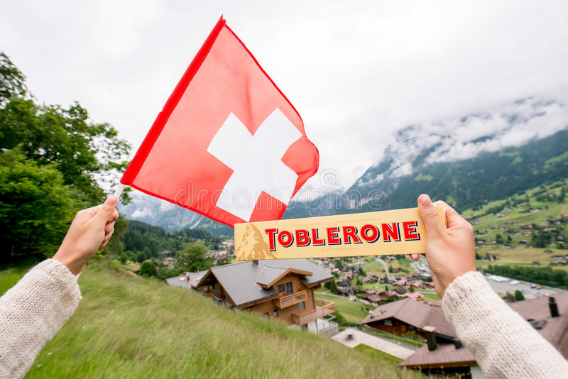 Toblerone bar chocolate. Grindelwald, Switzerland - June 26, 2016 Female hand holds Toblerone chocolate with swiss flag on the mountains background in royalty free stock photos