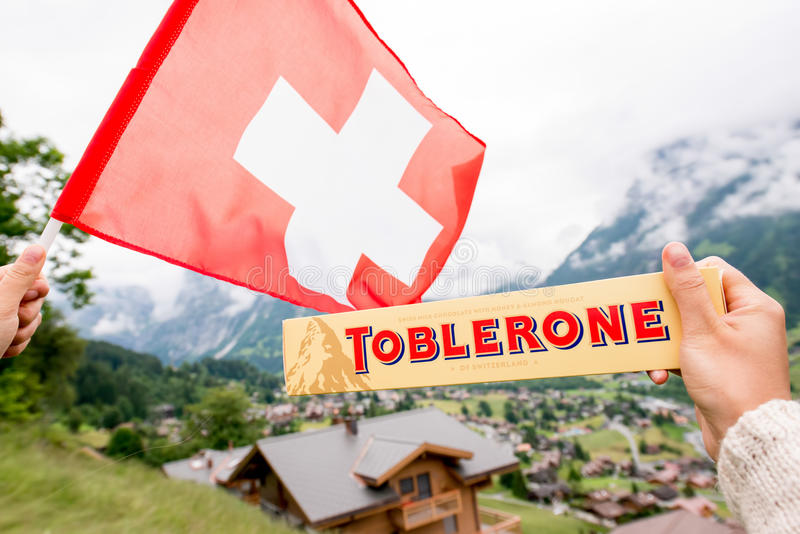 Toblerone bar chocolate. Grindelwald, Switzerland - June 26, 2016 Female hand holds Toblerone chocolate with swiss flag on the mountains background in stock photos