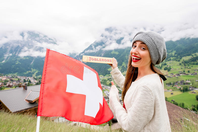 Toblerone bar chocolate. Grindelwald, Switzerland - June 26, 2016 Young woman holds Toblerone chocolate with Swiss flag on the mountains background in stock image