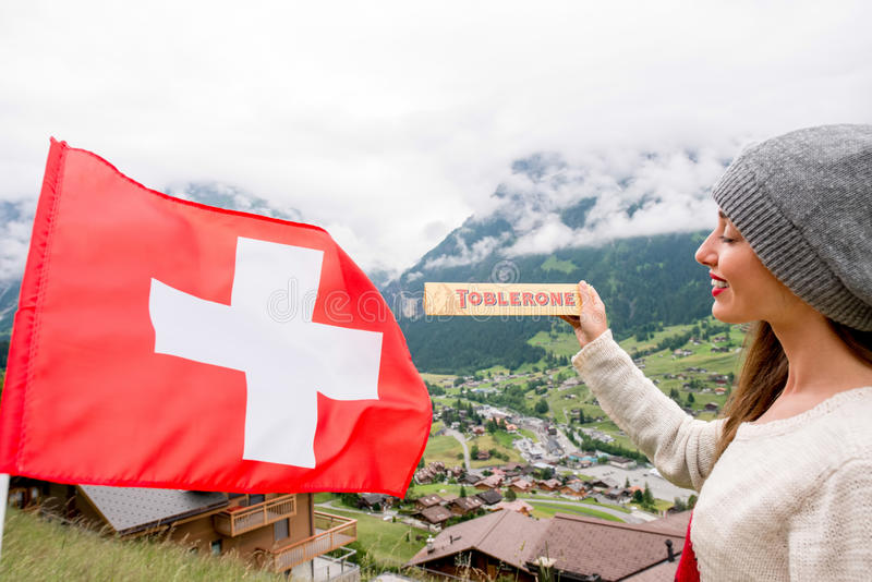 Toblerone bar chocolate. Grindelwald, Switzerland - June 26, 2016 Young woman holds Toblerone chocolate with Swiss flag on the mountains background in royalty free stock image