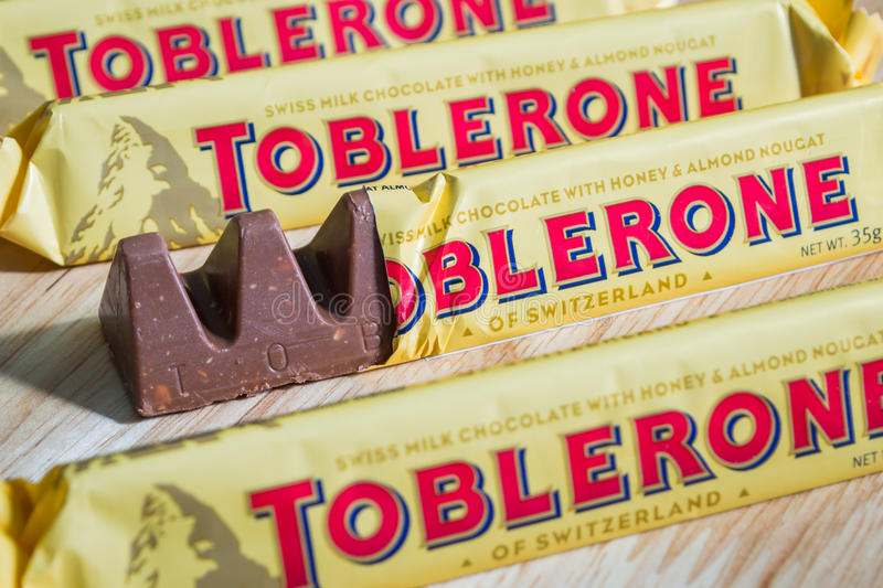TOBLERONE chocolate bars. Bangkok, Thailand - November 28, 2016: Toblerone chocolate bars - Swiss milk chocolate with honey and almond nougat on a wood stock photo