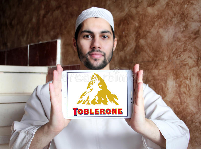 Toblerone chocolate logo. Logo of chocolate brand toblerone on samsung tablet holded by arab muslim man stock images