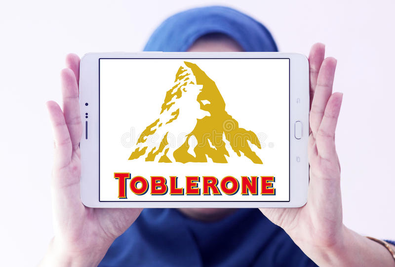 Toblerone chocolate logo. Logo of chocolate brand toblerone on samsung tablet holded by arab muslim woman royalty free stock images