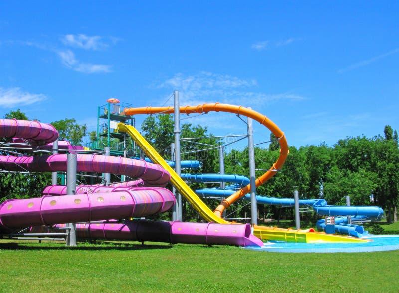 Toboganes acuáticos y piscina, aquapark en el parque verde fotografía de archivo