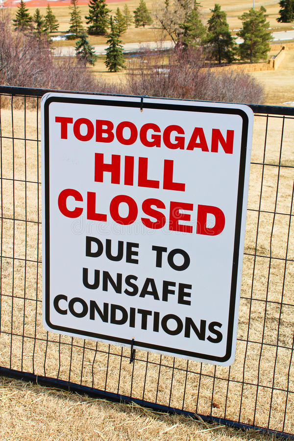 Toboggan hill closed sign posted in a public park once all the snow has melted stock photography