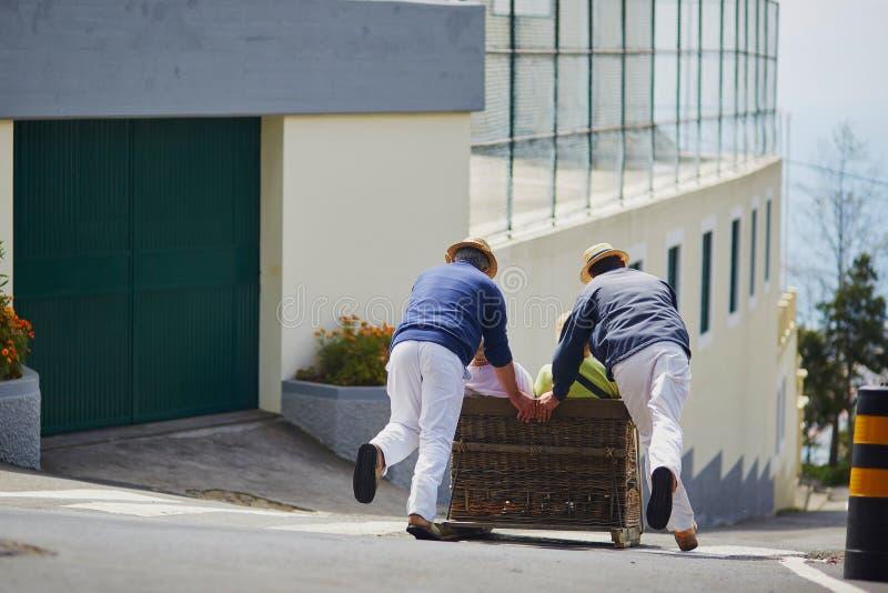 Toboggan ruiters die rietslee bergaf op de straten het eiland van van Funchal, Madera bewegen stock foto's