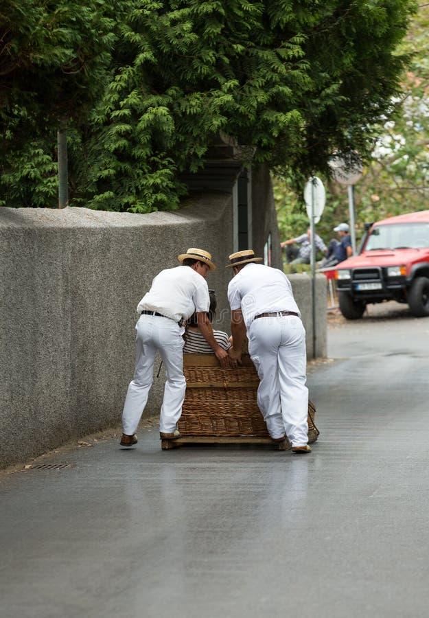 Toboggan ruiters die traditionele rietslee bergaf op de straten van Funchal bewegen Montepark, het eiland van Madera, stock afbeeldingen