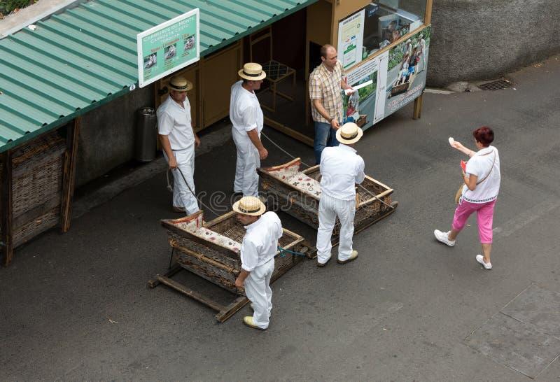 Toboggan ruiters die traditionele rietslee bergaf op de straten van Funchal bewegen Montepark, Madera royalty-vrije stock afbeelding
