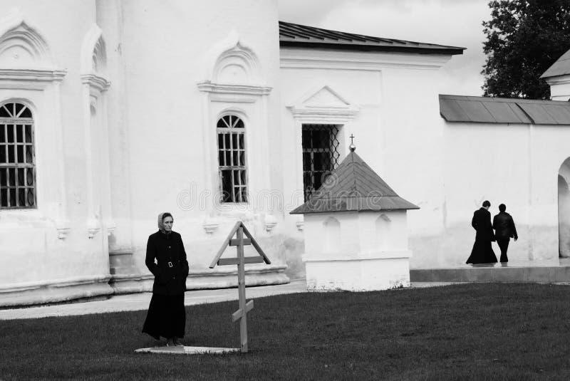 Tobolsk Ryssland, 10/05/2016: En kvinna besöker graven i en kloster I bakgrunden är prästerna svart white royaltyfri fotografi
