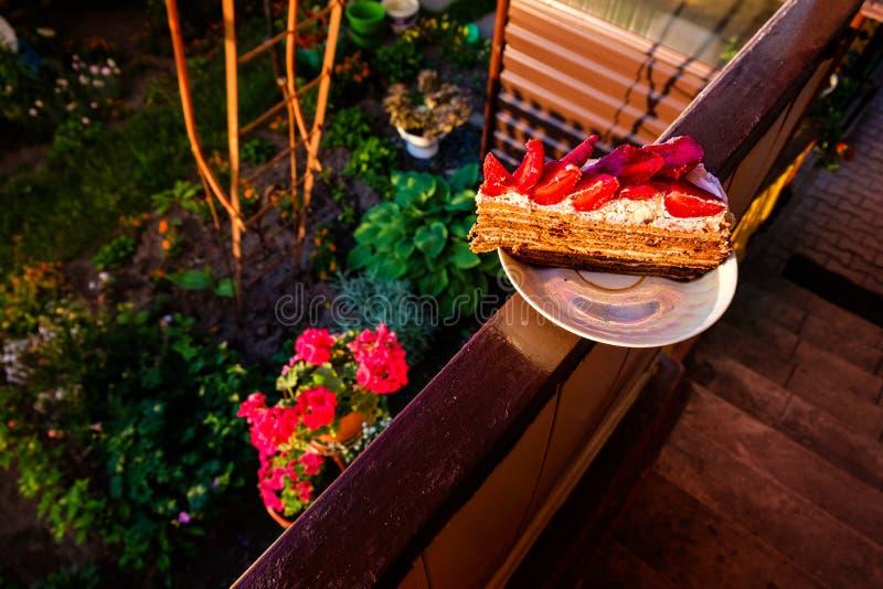 Tocado igualando el pedazo delicioso de la luz del sol de torta hecha en casa con la fresa y la crema azotada en una placa blanca imágenes de archivo libres de regalías