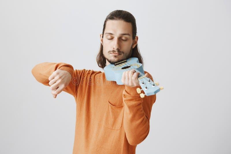 Tocando em nossas almas com cordas Indivíduo europeu engraçado emotivo na camiseta alaranjada que faz a expressão séria, guardand imagens de stock royalty free