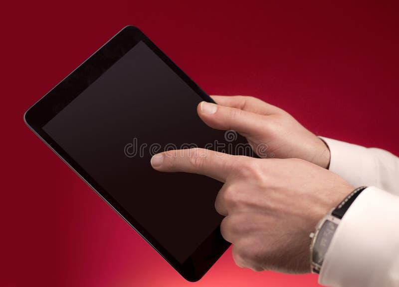 Tocando em uma tabuleta no vermelho fotos de stock