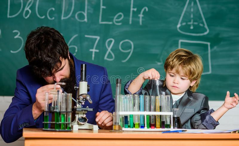 Tocando em vidas para sempre pai e filho na escola homem do professor com rapaz pequeno equipamento de laboratório da escola De v foto de stock royalty free