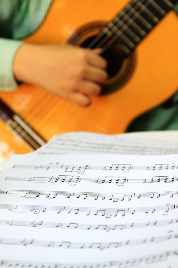 Tocar la guitarra clásica con la cuenta de la música foto de archivo libre de regalías