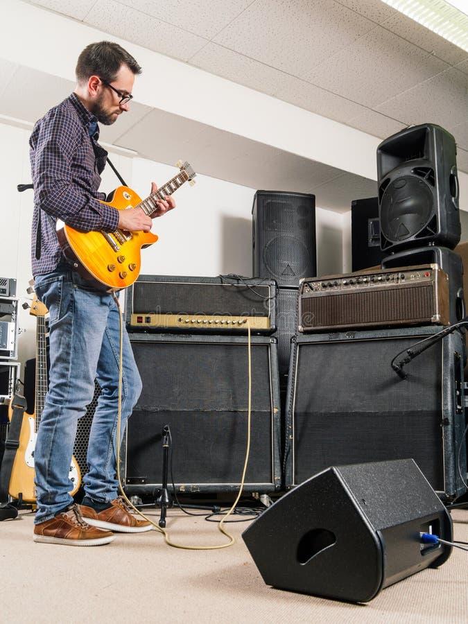 Tocar la guitarra eléctrica en un cuarto del atasco imagen de archivo